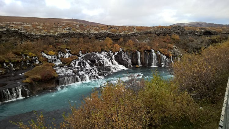 Hraunfossar is a series of waterfalls that come pouring out of porous lava rock.