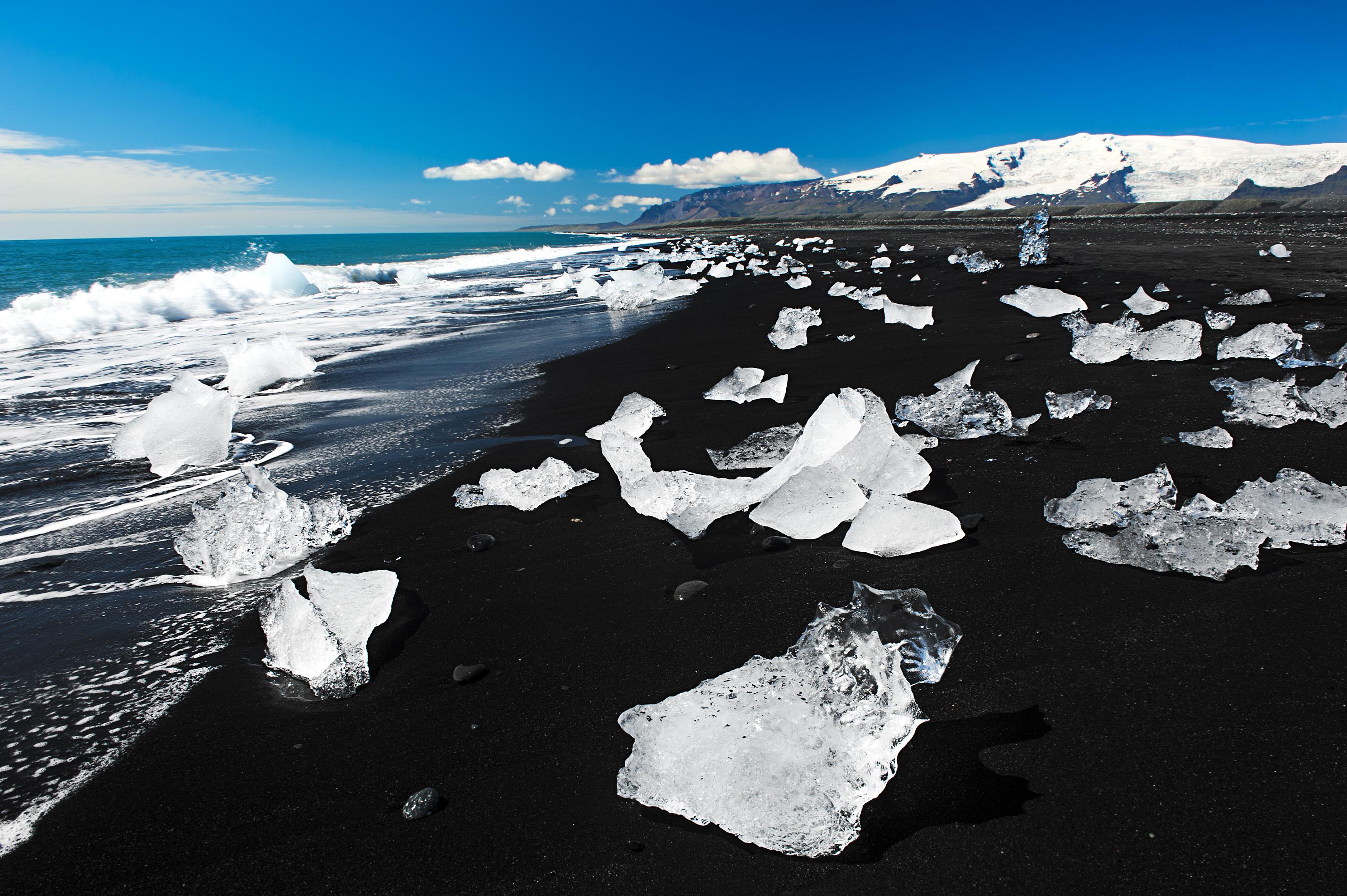 Białe góry lodowe ostro kontrastują z czarnym piaskiem na Diamentowej Plaży na południowym wybrzeżu Islandii.