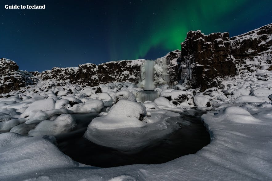 Öxaráfoss freezes solid during the winter; here, it is pictured beneath the aurora borealis.