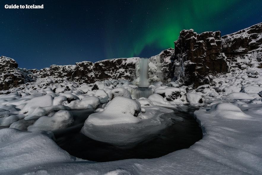 Der Öxarárfoss friert im Winter ein; hier ist er unter dem Polarlicht abgebildet