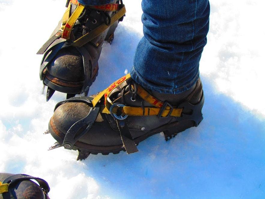 Pour une randonnée sur glacier en Islande, les crampons sont fixés sur la chaussure