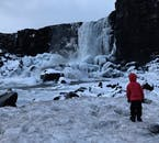 The beautiful Öxárfoss waterfall cascading down dark cliffs in Þingvellir National Park.