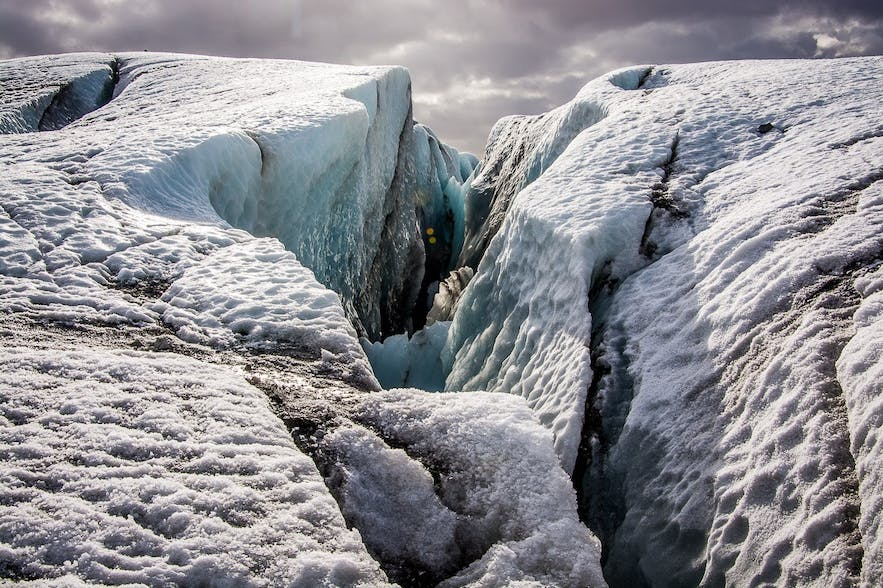 The movement of glaciers creates tensile strain on their brittle upper sections, causing them to break and create crevasses.