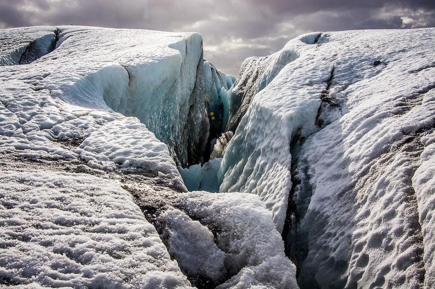 Die Bewegung der Gletscher verursacht Zugbelastung an den spröden oberen Abschnitten und führt zu Brüchen und zur Entstehung von Spalten