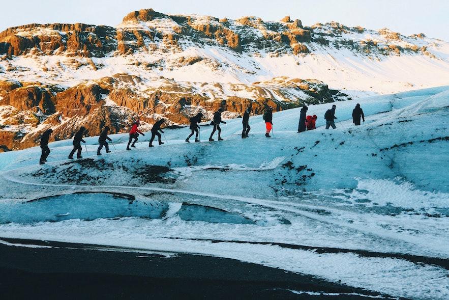 Randonneurs en ligne lors de leur randonnée sur glacier au Solheimajökull.