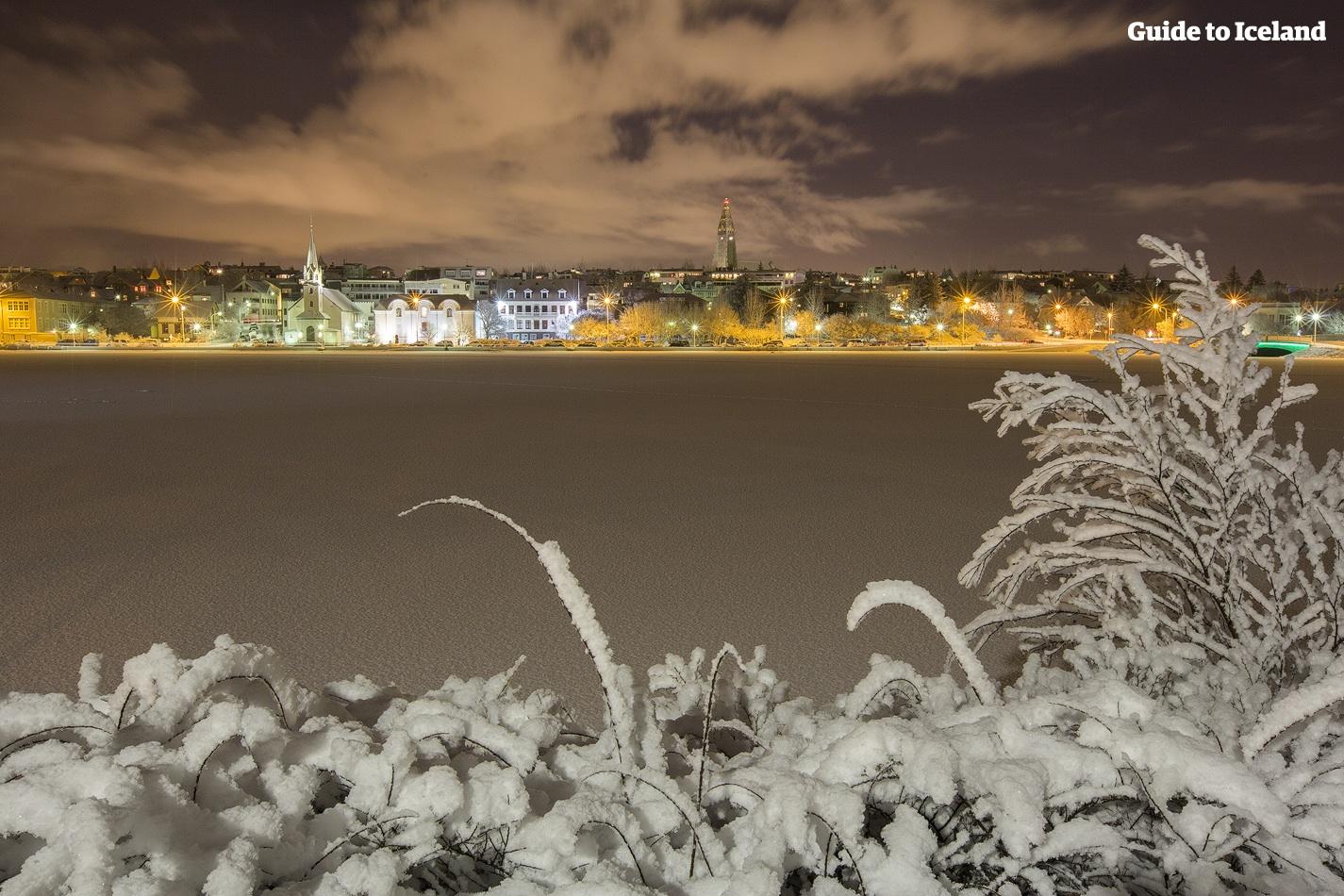 Das goldene Leuchten der Skyline von Reykjavík über dem gefrorenen See Tjörnin im Winter.