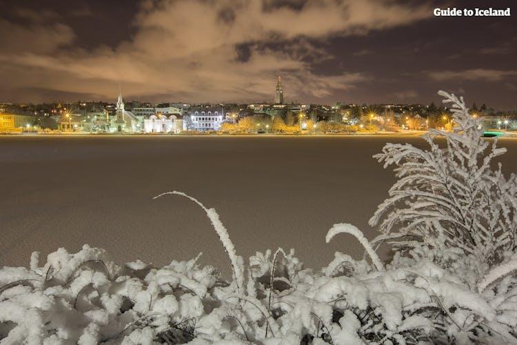 The skyline of Reykjavík glows a golden hue across the frozen Tjörnin Pond in winter.