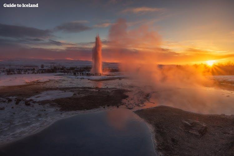Zachód zimowego słońca podczas erupcji gejzera Strokkur, stanowiącego część trasy Złotego Kręgu.