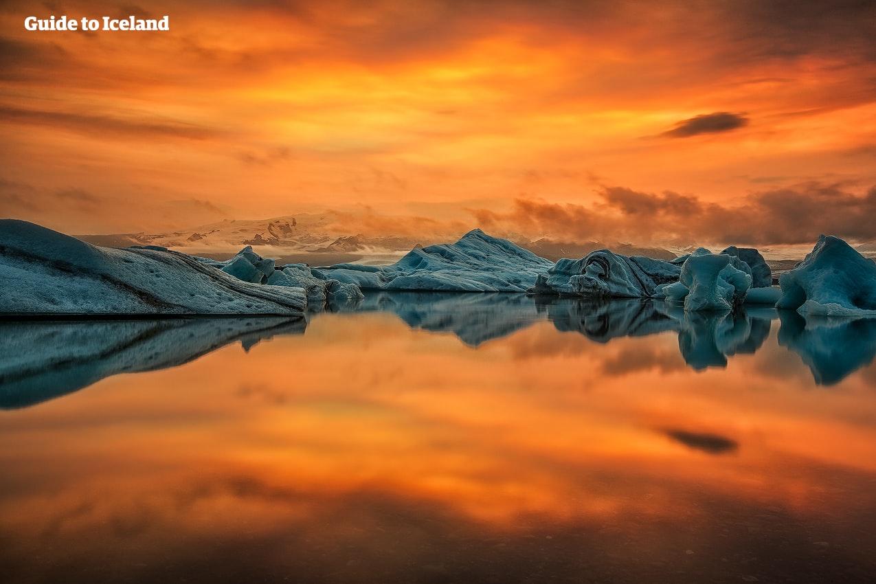 Die Reflexion des flammenden Himmels einer winterlichen Abenddämmerung in Island in der spiegelartigen Oberfläche der Gletscherlagune Jökulsárlón bildet einen spektakulären Kontrast zu den azurblauen Eisbergen.