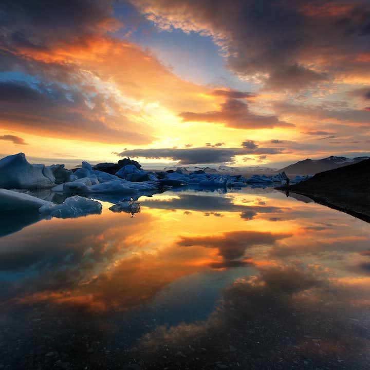 The colourful sky reflecting perfectly on the still surface of Iceland's deepest lake, Jökulsárlón glacier lagoon.
