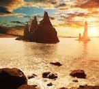 The Reynisdrangar sea-stacks caught in the stunning orange glow of the summer sun at night.
