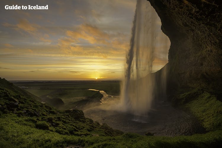From the cave behind Seljalandsfoss waterfall in south Iceland, visitors can admire the midnight sun through a veil of water.