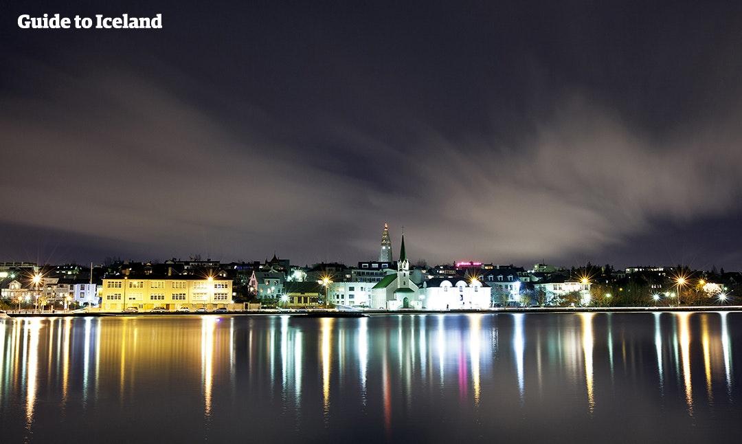 Wieczór w Reykjaviku, w tle ciepłe światło pochodzące z ulic i domów.