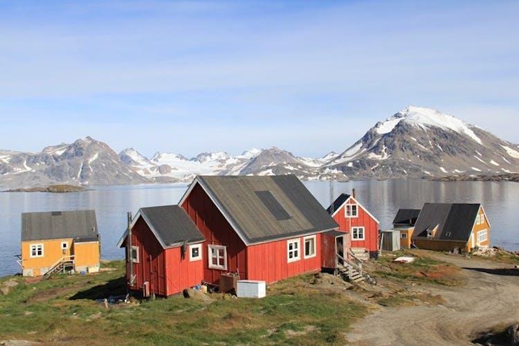 Traditionale, bunte Häuser unter der Mitternachtssonne in Kulusuk, Grönland