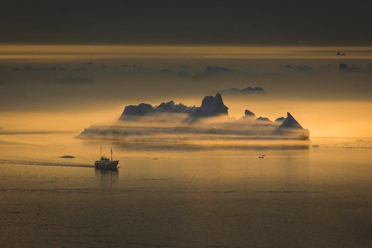 Dryfująca góra lodowa w trakcie zachodu słońca na Grenlandii.