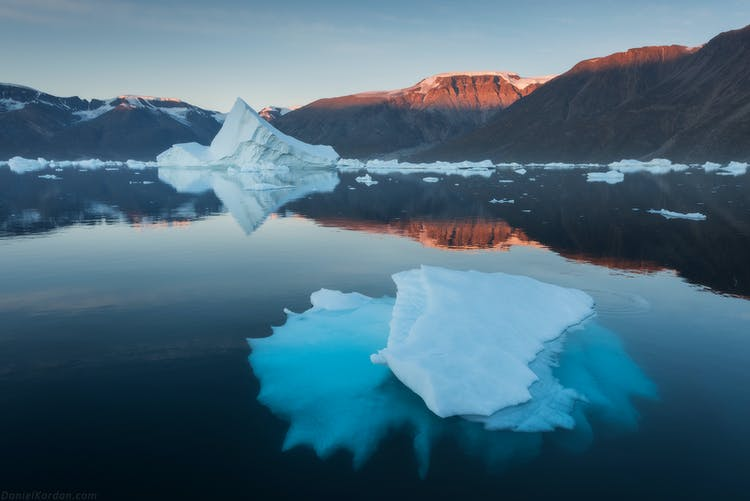 East Greenland is a land of enormous table-top mountains, plunging fjords, and giant icebergs in summer.