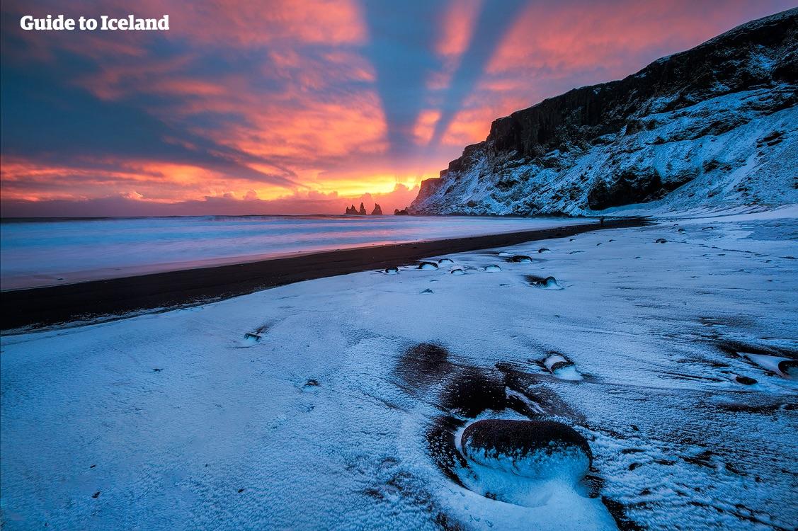 Reynisfjaras svarta sandstrand ligger täckt i snö medan vintersolens sista strålar målar himlen röd.