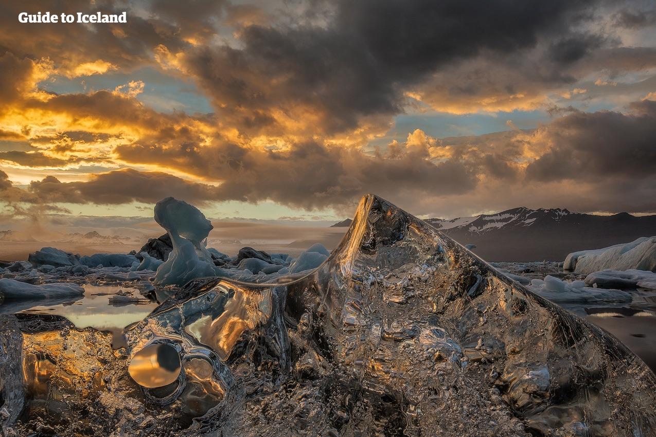 Vintersolens gyllene sken lyser upp issjön Jökulsárlón där kristallklara isberg driver omkring på vattnet.