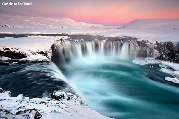 Der 30 Meter breite Goðafoss-Wasserfall, der im Winter über gefrorene Klippen hinabstürzt