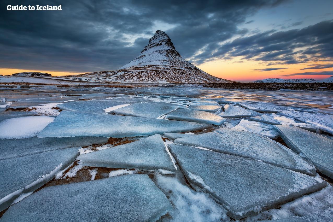 Et vinterlandskab på Snæfellsnes-halvøen, hvor det tilfrosne land omgiver Kirkjufell-bjerget