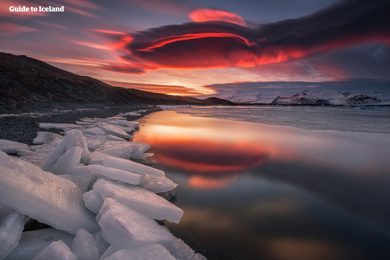 Die Sonne senkt sich über der Gletscherlagune Jökulsarlon und lässt den Himmel rot erstrahlen.