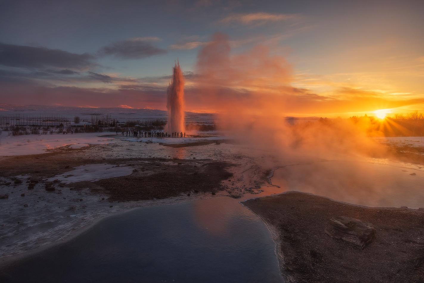 Strokkur sprøjter kogende vand op i luften ved solopgang.