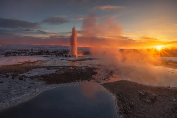 Вид на Гейзер Строккур, выбрасывающий столб кипящей воды, на рассвете.