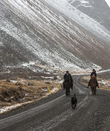 Reiten entlang einer isländischen Bergstraße im Winter