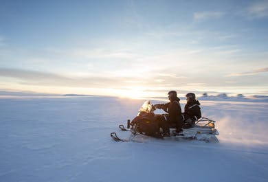 Snowmobilers rushing across the beautiful, icy surface of Langjökull Glacier
