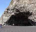 Le impressionanti scogliere di basalto della spiaggia di sabbia nera di Reynisfjara formano enormi caverne a lato del mare.