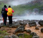 The landscape at Reykjadalur is a composition of lush green hills, steaming hot springs and dazzling rock formations.