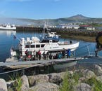 Enthusiastic sea-anglers getting ready to board a traditional vessel on a sunny day at the Snæfellsnes peninsula.