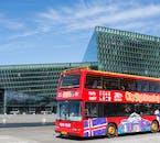 El autobús City Sightseeing fuera del exclusivo edificio de vidrio, la Sala de Conciertos y Conferencias Harpa.
