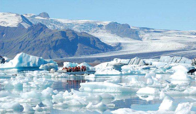 En båt seglar på issjön Jökulsárlón.