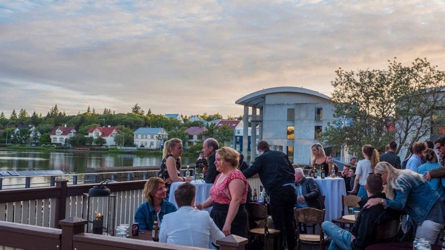 여름 밤 레이캬비크 호수 주변 파티오 아래에서 한가로운 시간을 보내는 아이슬란드 인들