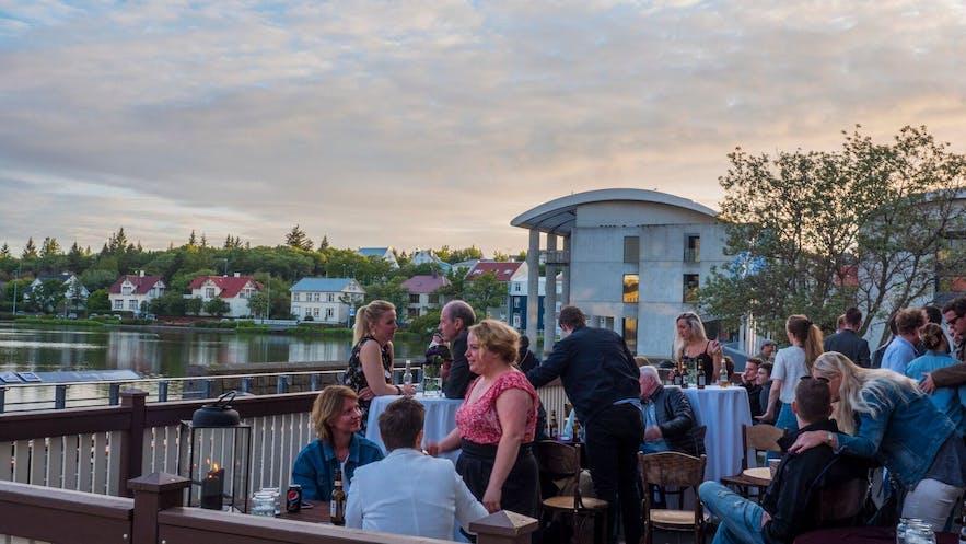 Les habitants profitant des rafraîchissements du patio de l'étang de Reykjavík par une nuit d'été
