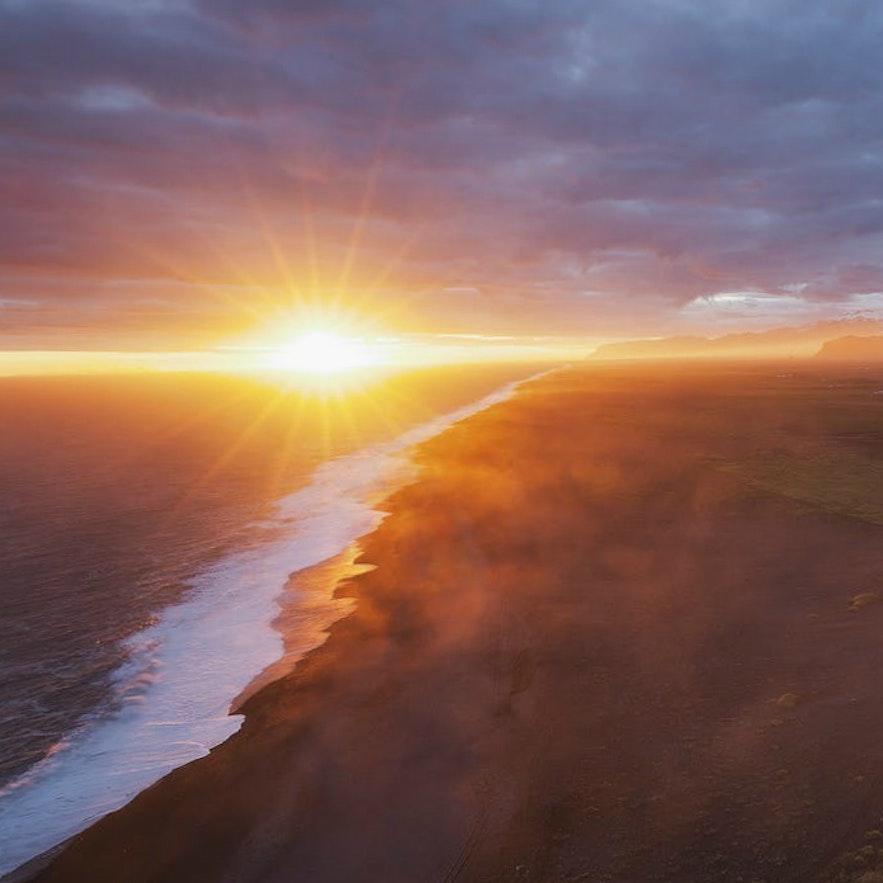 冰岛南岸迪霍拉里海岬山顶鸟瞰黑沙滩日落