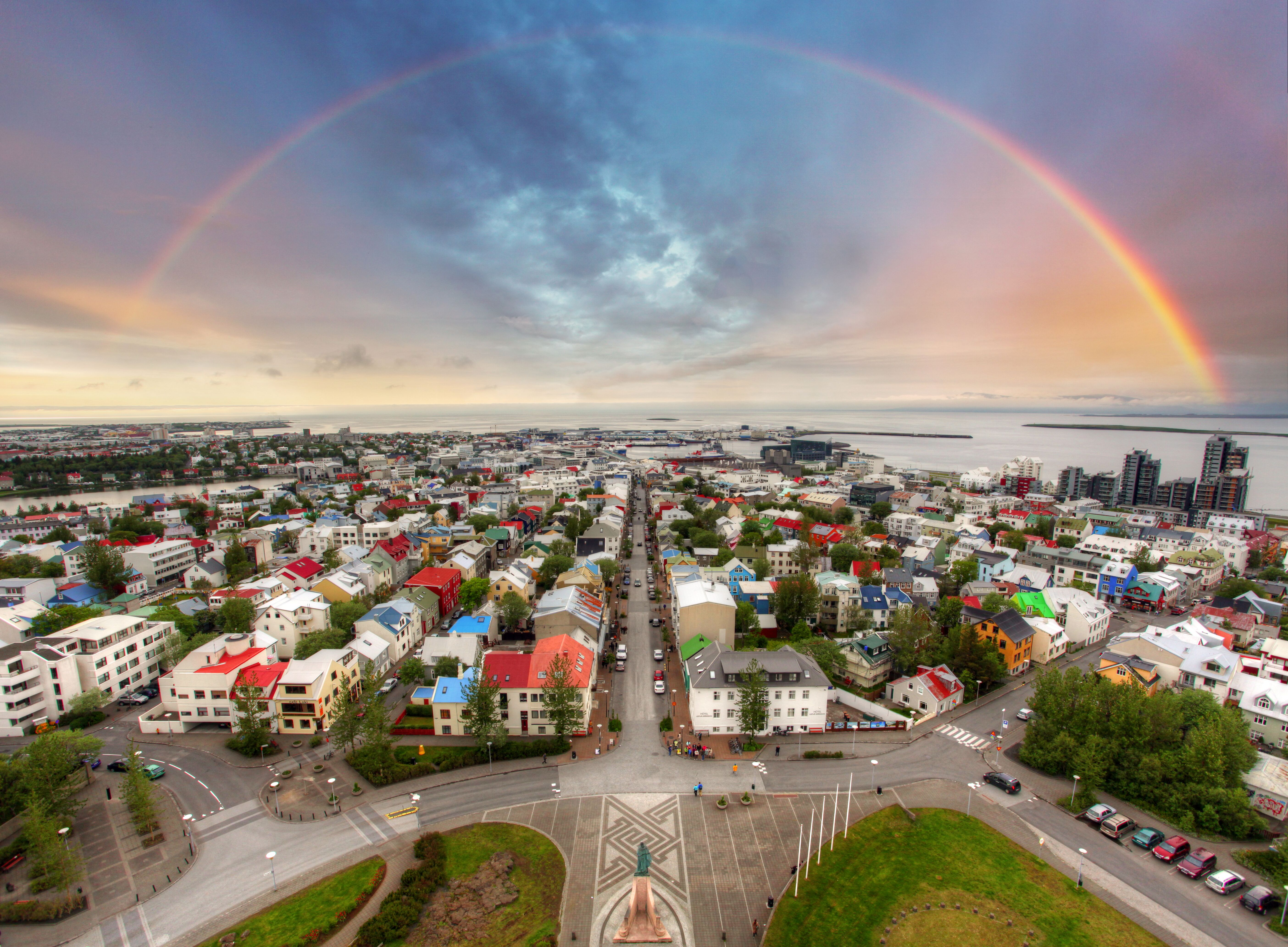 从冰岛首都景点哈尔格林姆斯大教堂(Hallgrímskirkja)俯瞰雷克雅未克彩色的小屋房顶以及悬挂在高空的彩虹