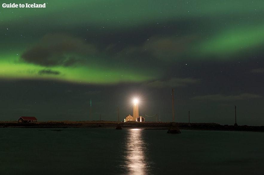 Zorza polarna tańcząca nad latarnią morską