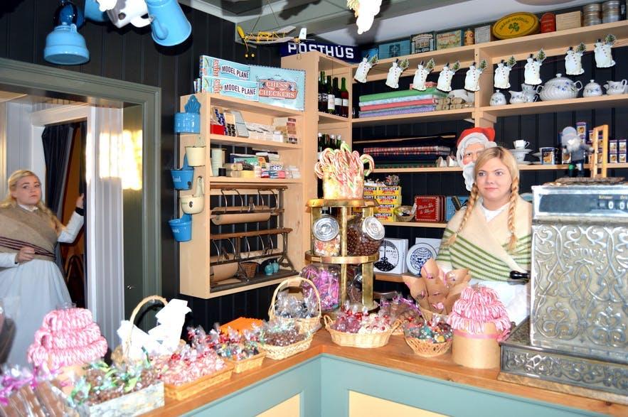 크리스마스 기념품과 과자류를 팔고 있는 상점. 여성 점원은 전통 복장을 착용하고 있습니다.