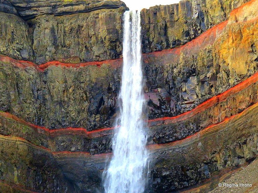 De rotsen achter de Hengifoss-waterval in Oost-IJsland hebben een mooi rode kleur