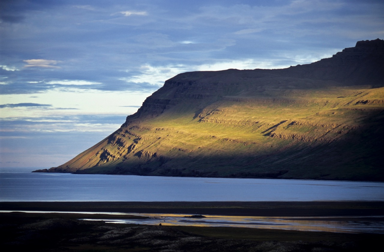 A ray of sun lights up on of the beautiful mountains of the East Fjords in summer.
