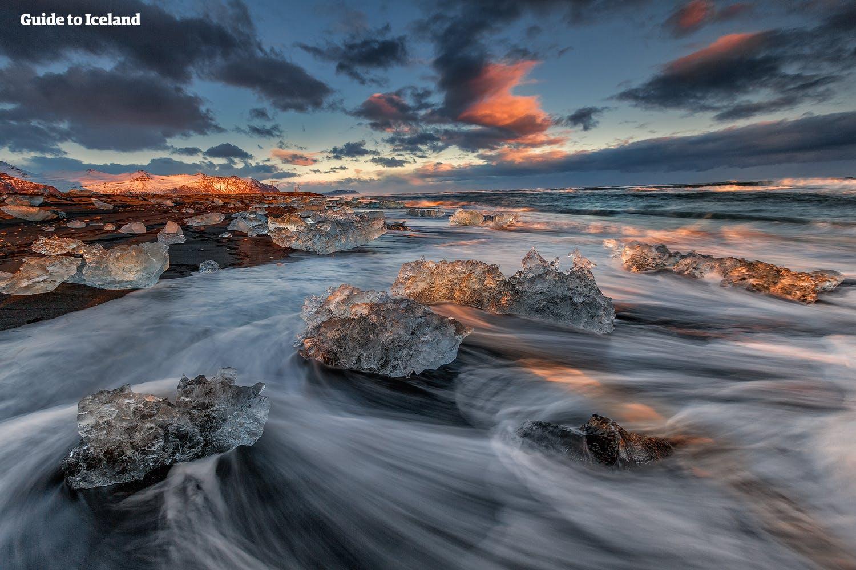Fotografen zullen het effect waarderen van de branding die speelt met de aangespoelde ijsbergen op Diamond Beach in Zuidoost-IJsland.