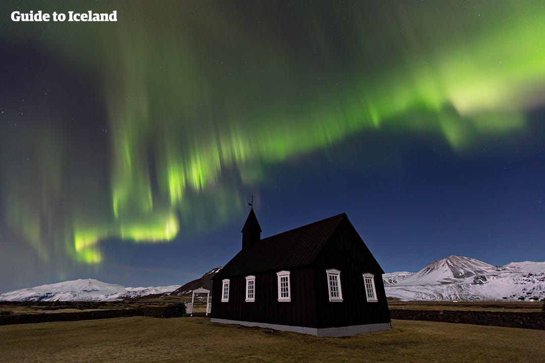 De Snæfellsjökull-gletsjer doemt op achter de kerk in Buðir, hier afgebeeld onder een heldere hemel vol dansende noorderlichten.