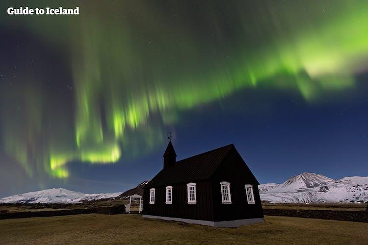 Il ghiacciaio Snæfellsjökull incombe dietro la chiesa di Budir, qui sotto un cielo limpido, pieno di aurore danzanti.