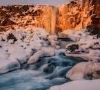 オクサルアゥフォスの滝が冬の太陽の光に照らされて朱く染まる
