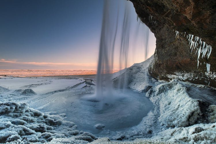 Although you can walk behind Seljalandsfoss waterfall in the summer, it is not safe to do so in winter because the ground is covered with ice.