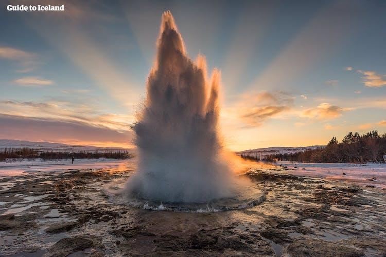 日の出を背景に勢いよく噴き上げるストロックル間欠泉