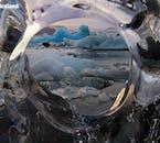 มองผ่านน้ำแข็งประกายใสในโจกุลซาลอนเผยให้เห็นความงามอันยิ่งใหญ่ของทะเลสาบธารน้ำแข็ง.