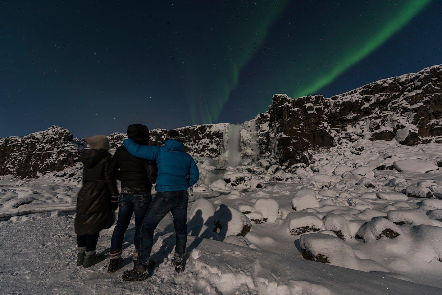 Grupa podróżników w Parku Narodowym Thingvellir zachwyca się pokazem zorzy polarnej.